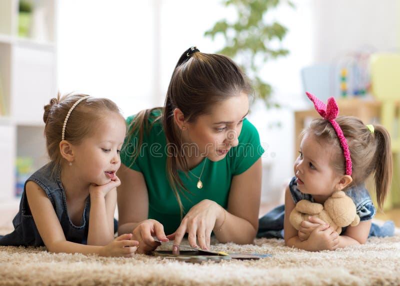 Mãe nova que lê um livro a suas filhas das crianças Crianças e mamã que encontram-se no tapete na sala de visitas ensolarada fotos de stock