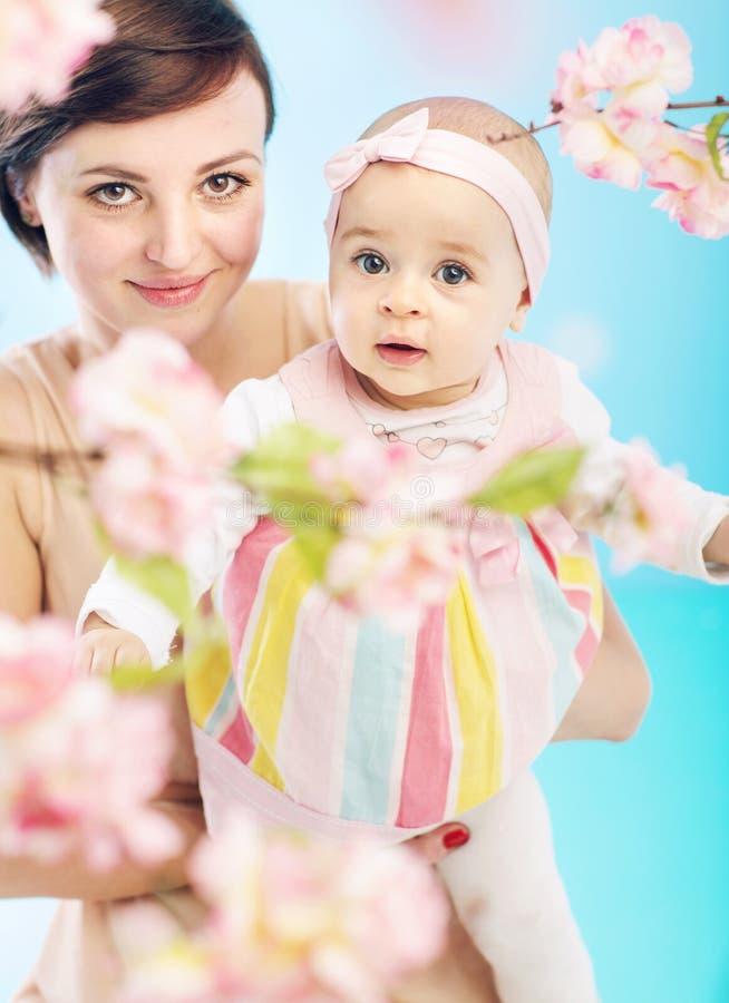 Mãe nova que leva a filha pequena bonito foto de stock