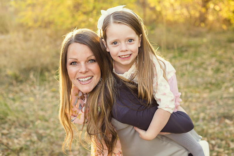 Mãe nova que leva seu reboque bonito da filha imagens de stock royalty free
