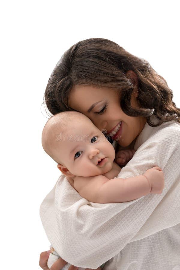Mãe nova que mantém o bebê bonito em seus braços imagens de stock royalty free