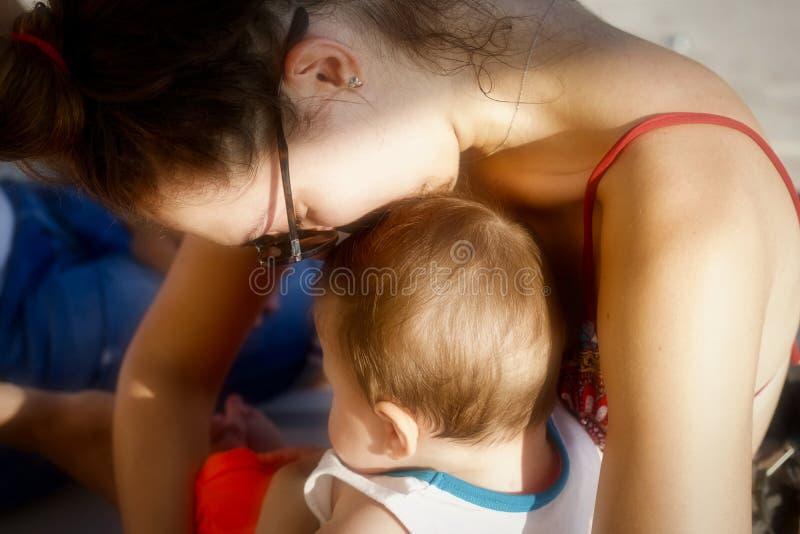 Mãe nova que protege e que beija seu bebê na praia fotos de stock royalty free