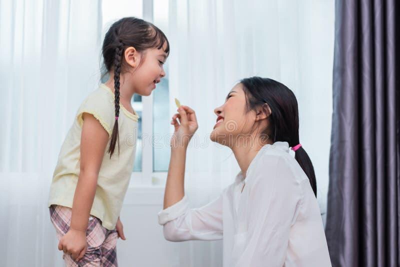 Mãe nova que relaxa junto com sua criança pequena Menina adorável da criança na casa que come a microplaqueta de batata com mamã  foto de stock