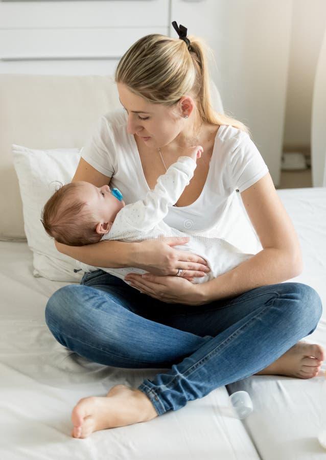 Mãe nova que senta-se na cama com seus 3 meses do bebê idoso foto de stock royalty free