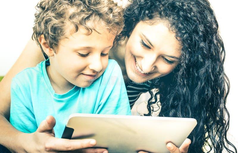 Mãe nova que tem o divertimento com o filho que usa a tabuleta na cama - aprendendo junto imagem de stock