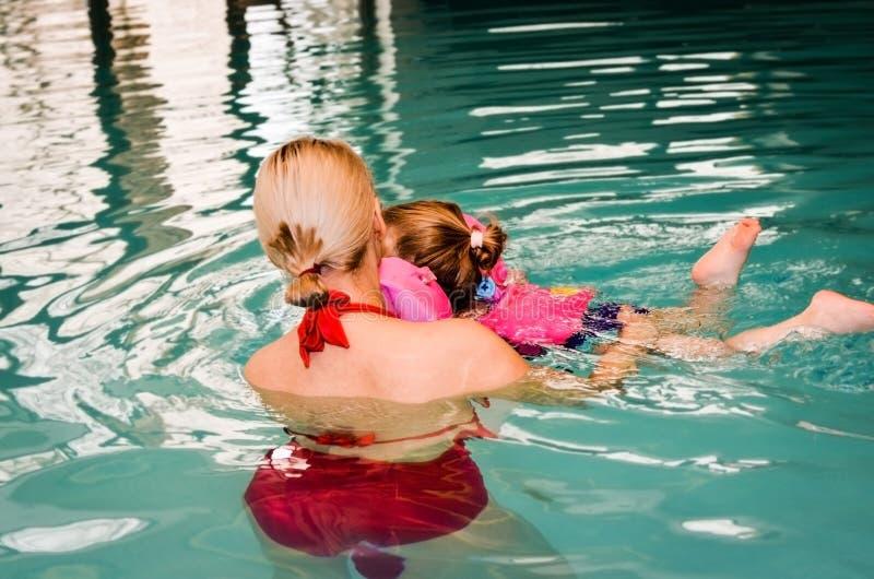 Mãe nova que tenta aprender nadar em sua filha pequena na piscina interior filtro do vintage imagens de stock