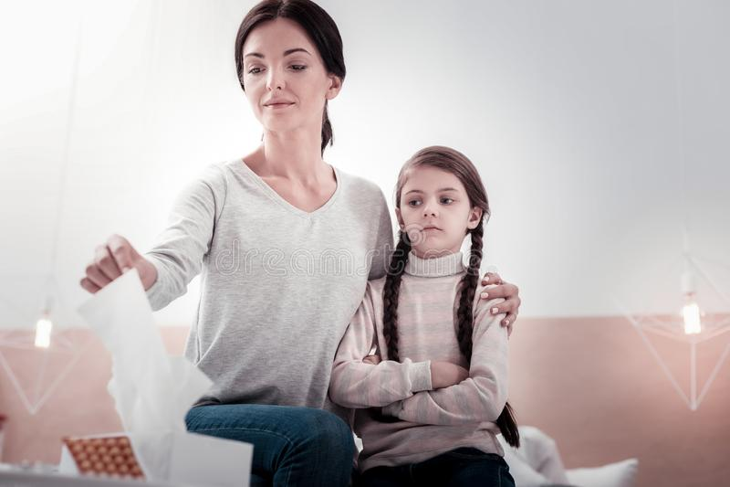 Mãe nova que toma guardanapo ao sentar-se com sua filha foto de stock