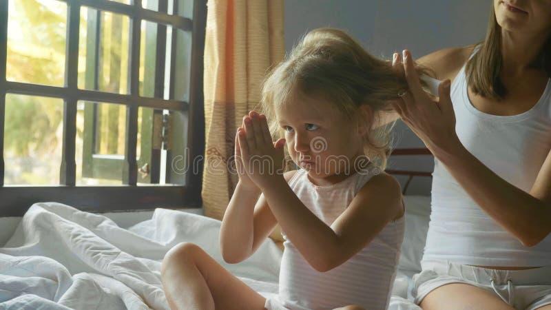 A mãe nova senta-se na cama e em pentear sua filha fotos de stock