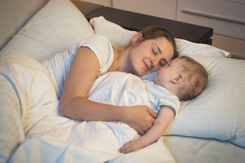 Mãe nova tonificada das FO do retrato que dorme na cama com seus 9 meses do filho idoso do bebê imagem de stock