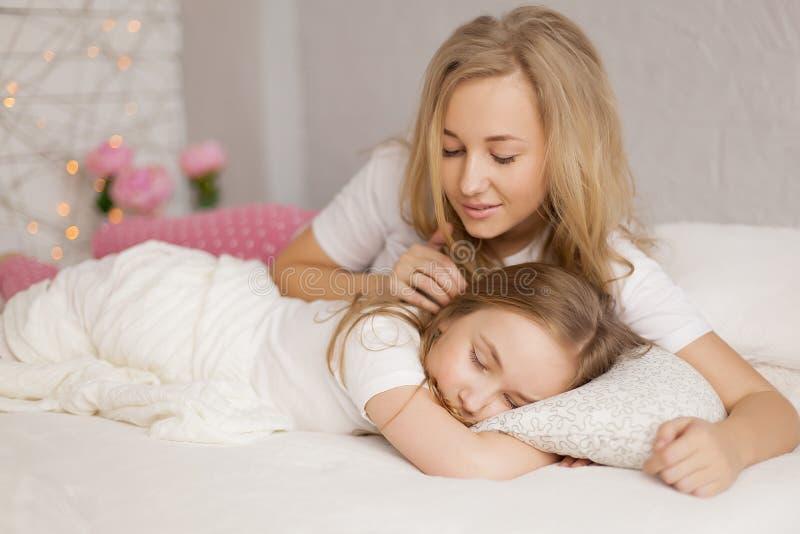 A mãe pôs sua filha para dormir interior Cuidado do conceito imagem de stock