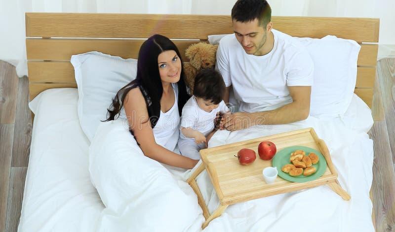 Mãe, pai, bebê na cama na sala fotos de stock