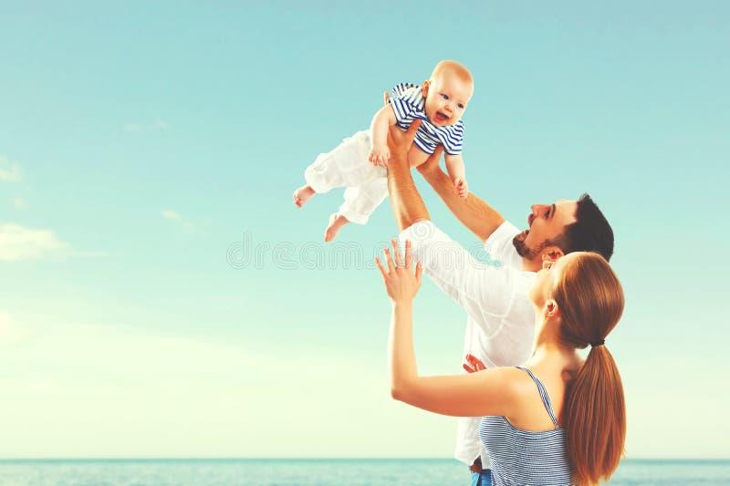 Mãe, pai e bebê felizes da família no mar imagem de stock royalty free
