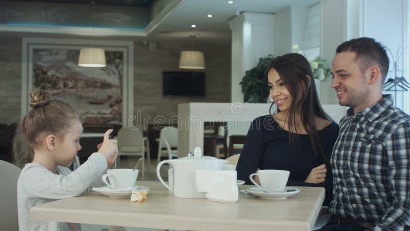 Mãe, pai feliz e menina tendo o jantar no café Caçoe a tomada da foto pelo smartphone quando os pais que levantam sobre fotografia de stock royalty free