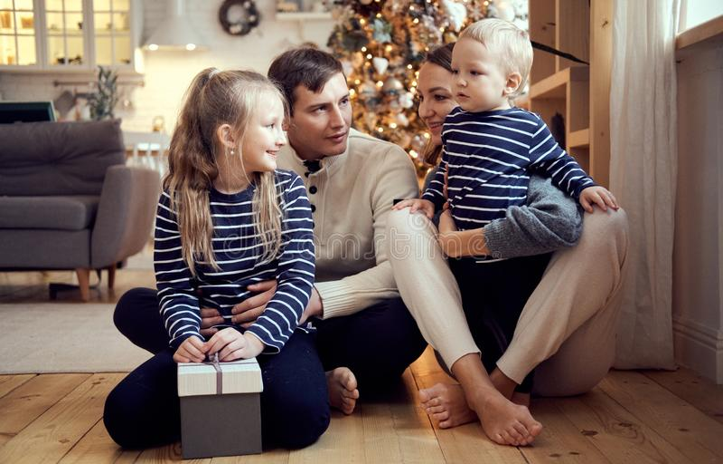 Mãe, pai, filho feliz e filha completos da família sentando-se no assoalho na Noite de Natal Retrato do Natal foto de stock