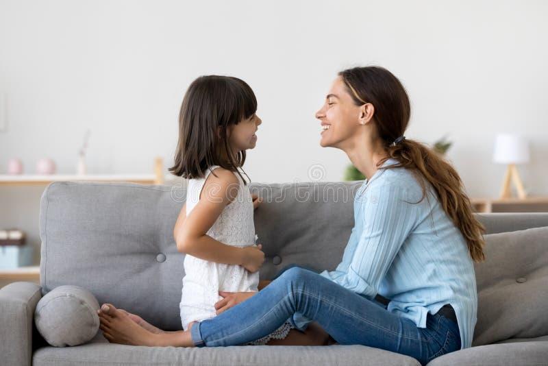 A mãe passa o tempo com pouco assento de fala da filha no sofá fotos de stock royalty free