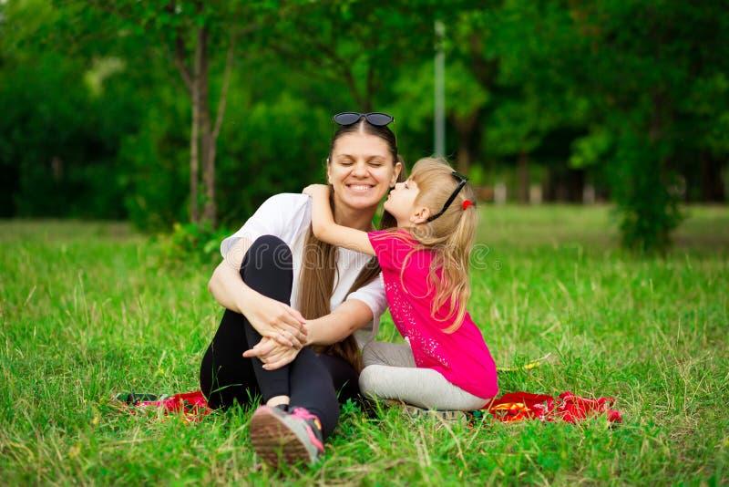 Mãe pequena bonita do beijo da filha Retrato exterior da família feliz Alegria feliz do dia do ` s da mãe fotografia de stock royalty free