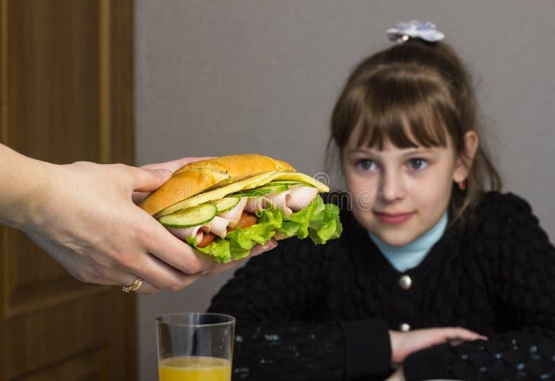 A mãe prepara um sanduíche para uma criança na escola fotografia de stock royalty free