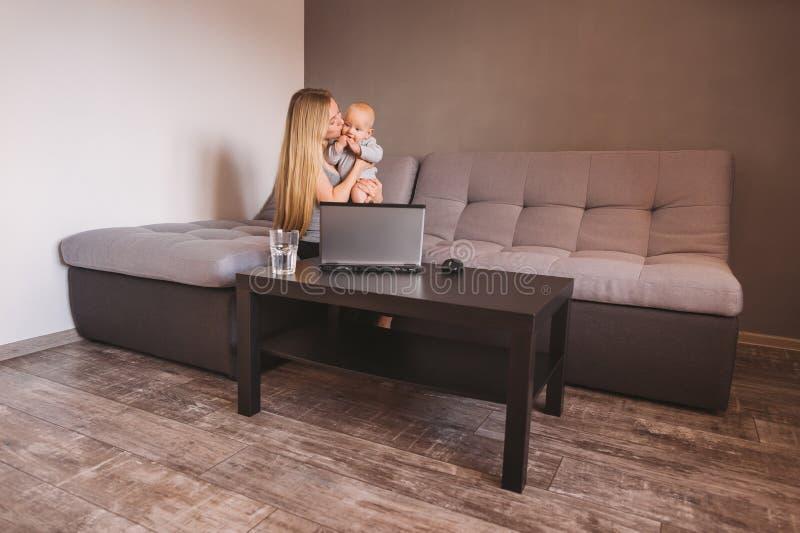 mãe que abraça pouca criança ao sentar-se no sofá fotos de stock