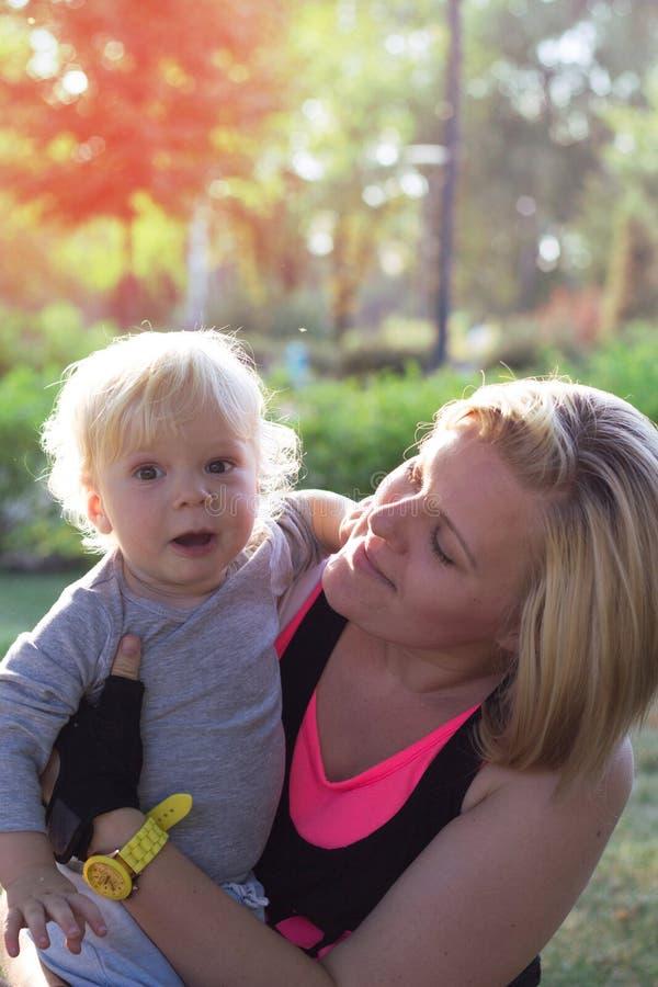 Mãe que abraça seu bebê no parque fotos de stock royalty free