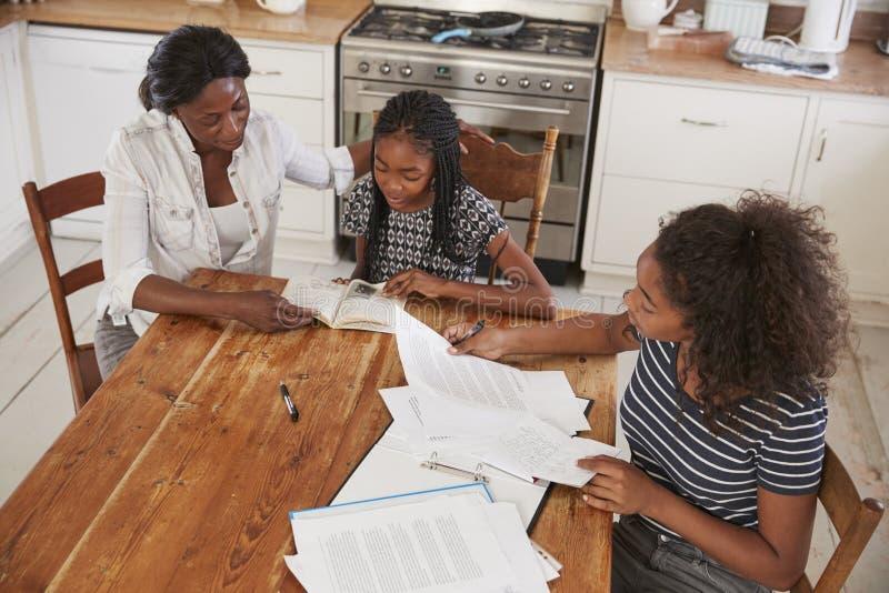 Mãe que ajuda duas filhas que sentam-se na tabela que faz trabalhos de casa foto de stock royalty free