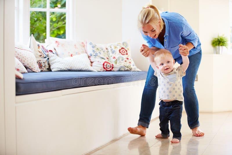 Mãe que ajuda o filho novo como aprende andar foto de stock