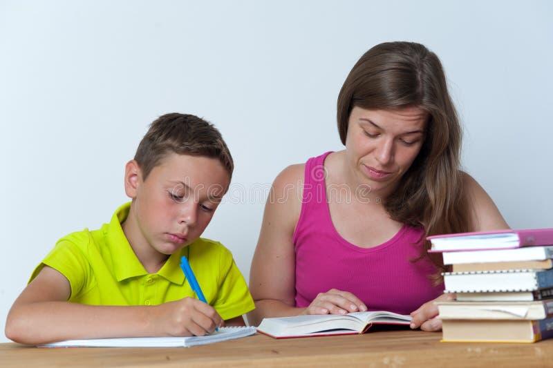 Mãe que ajuda seu filho com lições dos trabalhos de casa imagem de stock royalty free