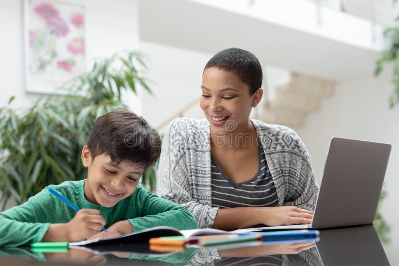Mãe que ajuda seu filho com seus trabalhos de casa em uma tabela imagens de stock royalty free
