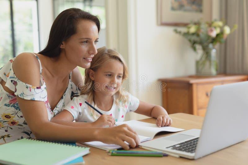 Mãe que ajuda sua filha com trabalhos de casa em uma casa confortável imagens de stock
