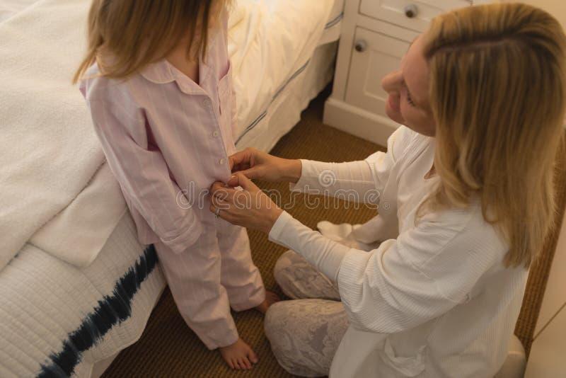 Mãe que ajuda sua filha no nightwear vestindo foto de stock royalty free