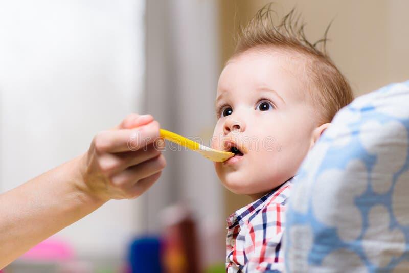 Mãe que alimenta seu dia do papa de aveia do peito do bebê fotografia de stock