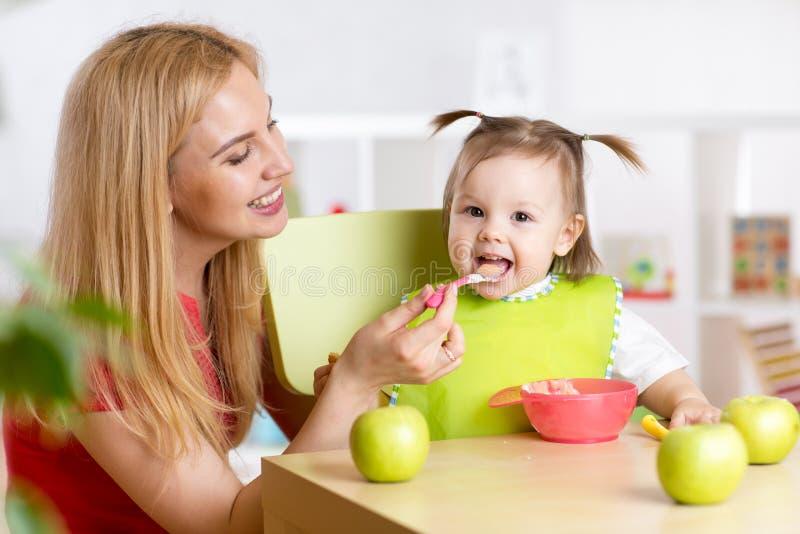 Mãe que alimenta a sua criança o alimento saudável imagens de stock royalty free