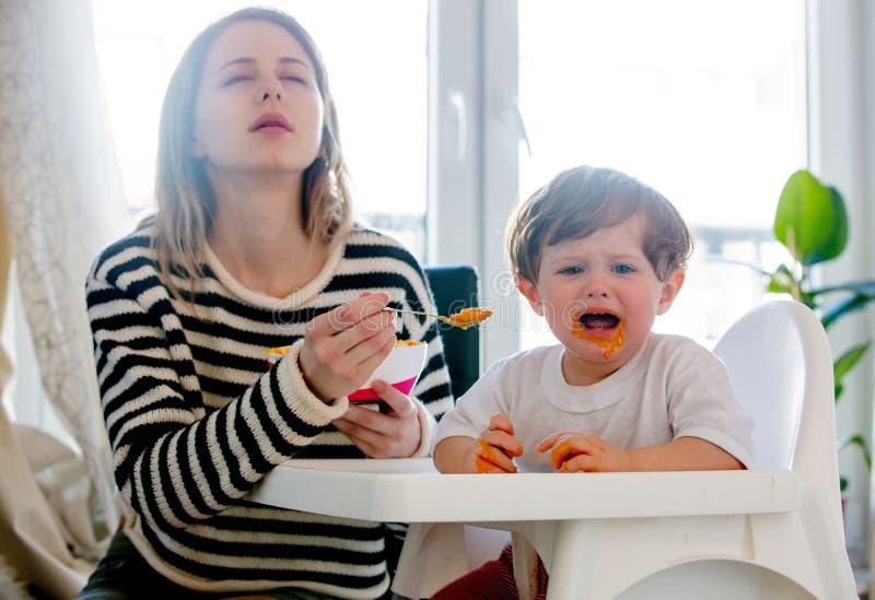 M?e que alimenta um menino da crian?a com uma colher e um c?o que olham nele fotos de stock