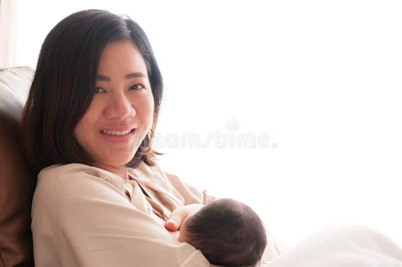 Mãe que amamenta seu bebê recém-nascido ao lado da janela O leite do peito do ` s da mãe é uma medicina natural ao bebê Dia da mã fotos de stock royalty free
