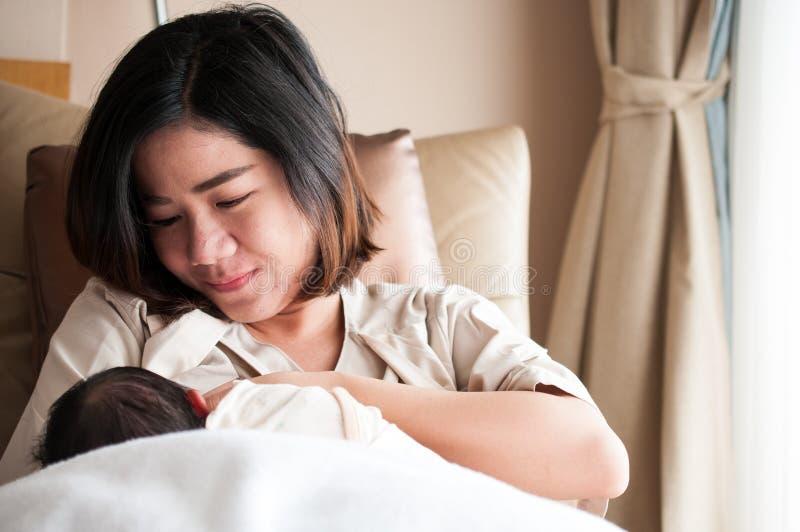 Mãe que amamenta seu bebê recém-nascido ao lado da janela O leite do peito do ` s da mãe é uma medicina natural ao bebê Dia da mã fotos de stock