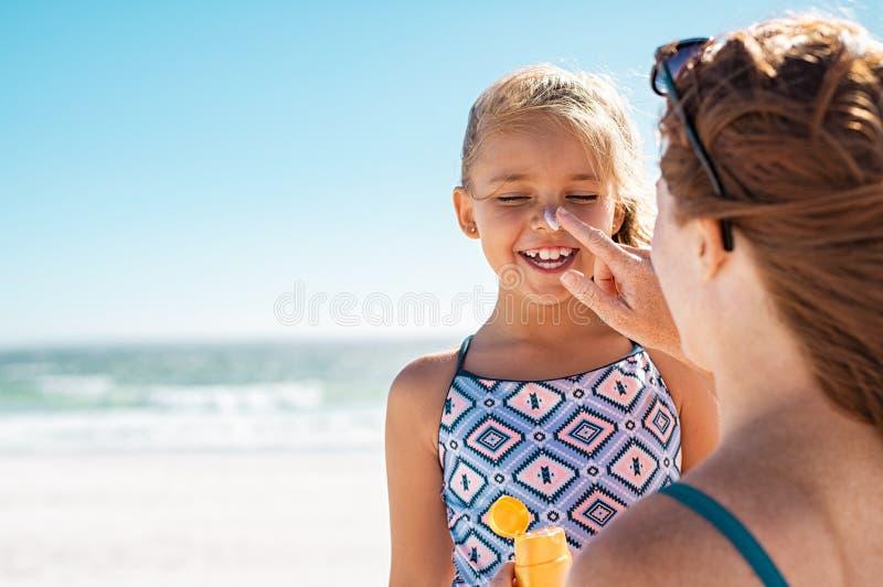 Mãe que aplica a loção para bronzear na cara da filha imagens de stock