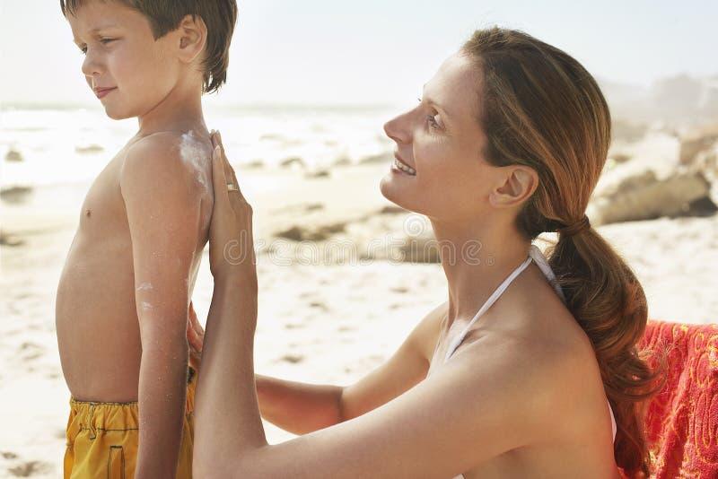 Mãe que aplica o creme da proteção solar na parte traseira do filho imagem de stock