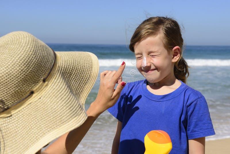 Mãe que aplica a proteção solar fotos de stock