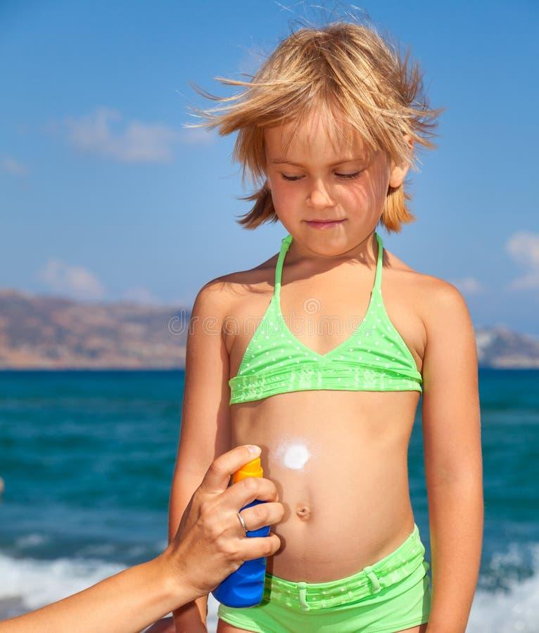 Mãe que aplica a proteção solar a sua criança foto de stock royalty free