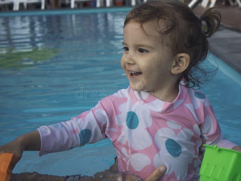 Mãe que aprecia um dia de verão na piscina com sua família fotos de stock royalty free