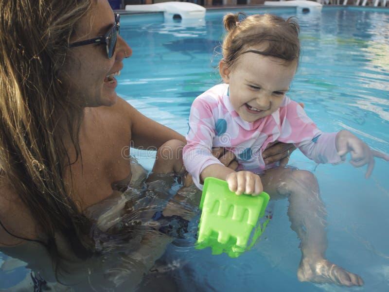 Mãe que aprecia um dia de verão na piscina com sua família fotos de stock
