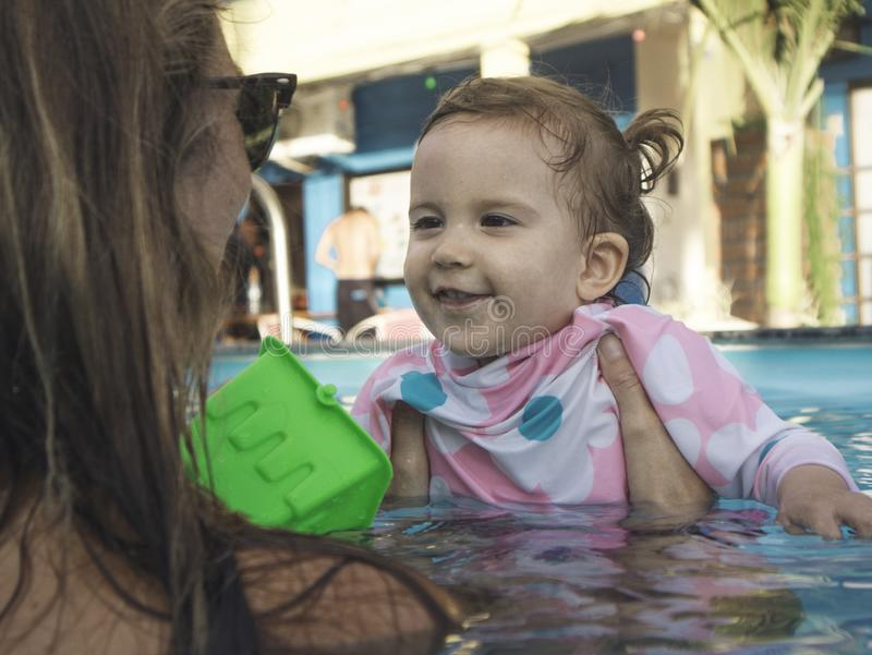 Mãe que aprecia um dia de verão na piscina com sua família imagens de stock royalty free