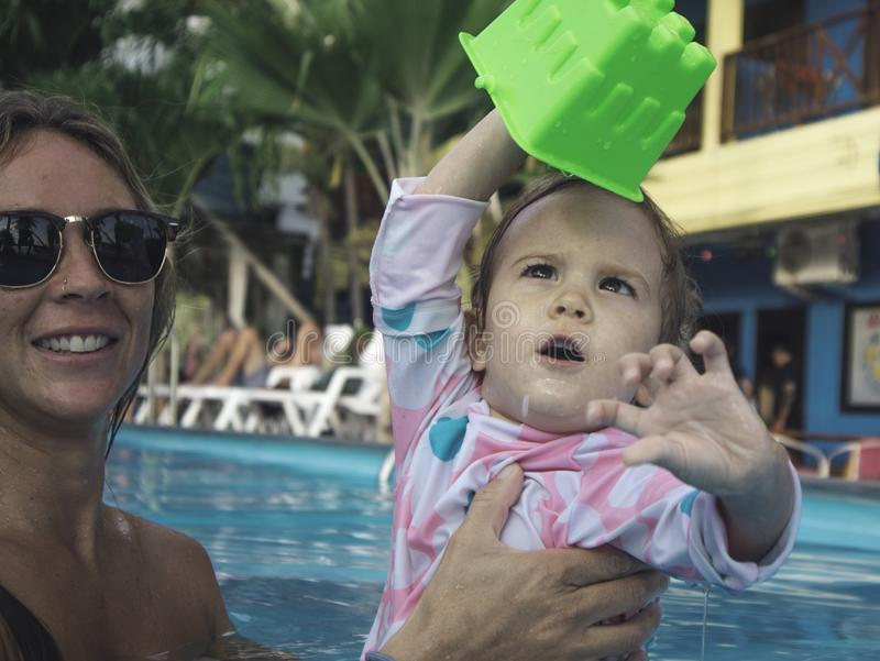Mãe que aprecia um dia de verão na piscina com sua família imagem de stock royalty free