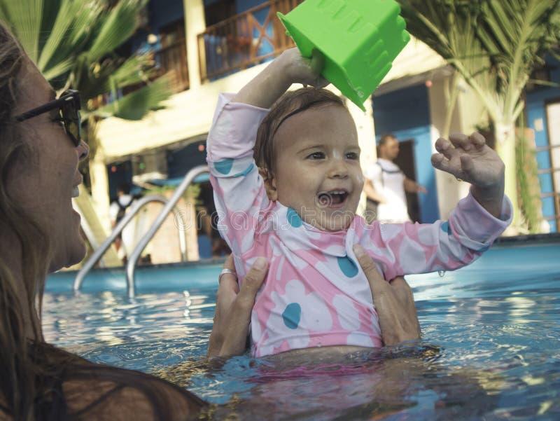 Mãe que aprecia um dia de verão na piscina com sua família imagens de stock