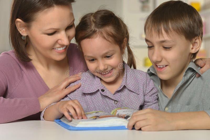Mãe que aprende lições com crianças imagem de stock