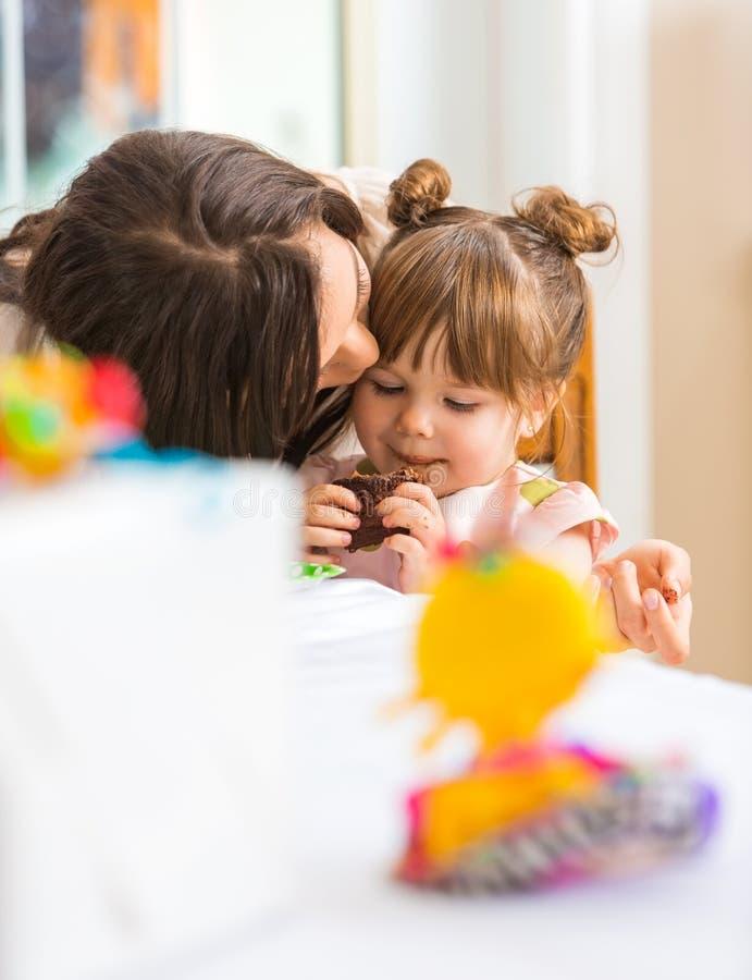 Mãe que beija a menina que come o queque fotografia de stock