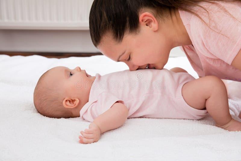 Mãe que beija no estômago de um bebê foto de stock