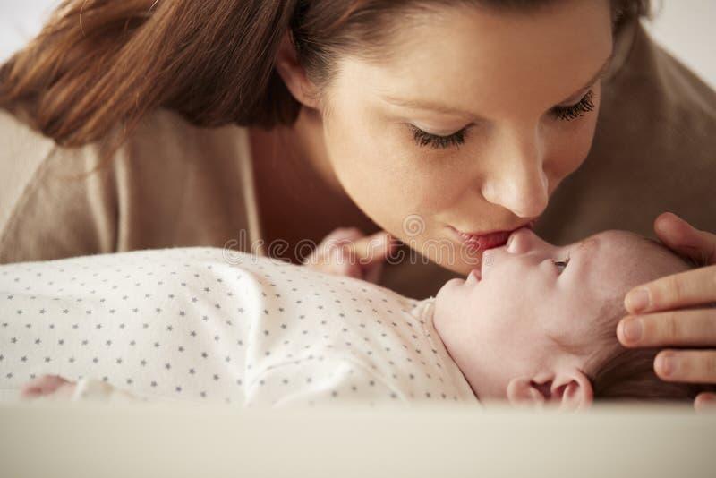 Mãe que beija o bebê recém-nascido que encontra-se na tabela em mudança no berçário imagens de stock royalty free