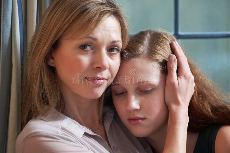 Mãe que consola a filha adolescente imagem de stock