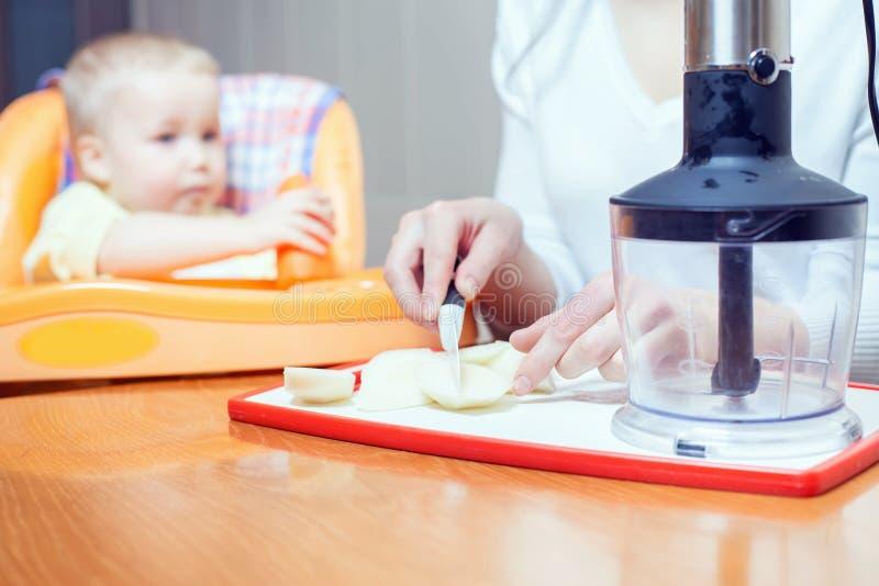 Mãe que cozinha no misturador puro para o bebê imagens de stock
