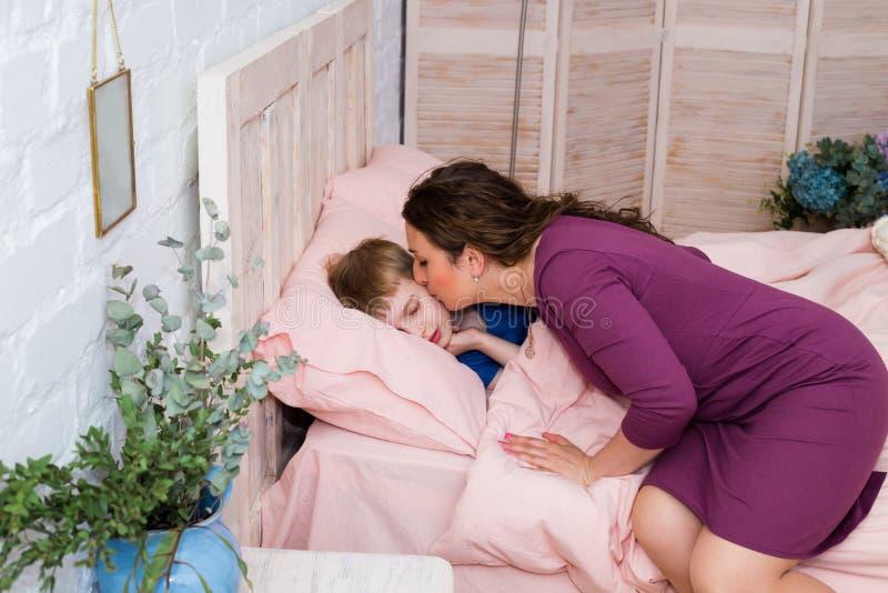 Mãe que dá o beijo da boa noite ao filho de sono Mãe bonita que põe o filho para colocar fotografia de stock royalty free