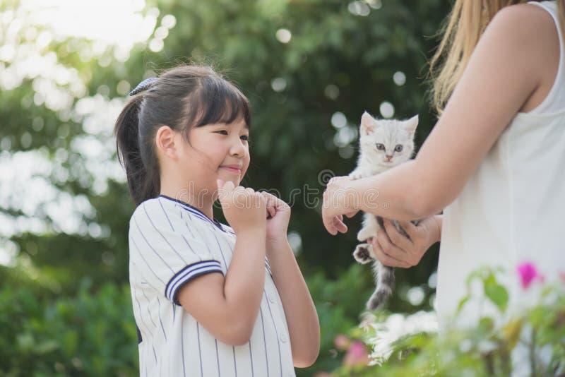 Mãe que dá um gatinho a sua filha fotografia de stock
